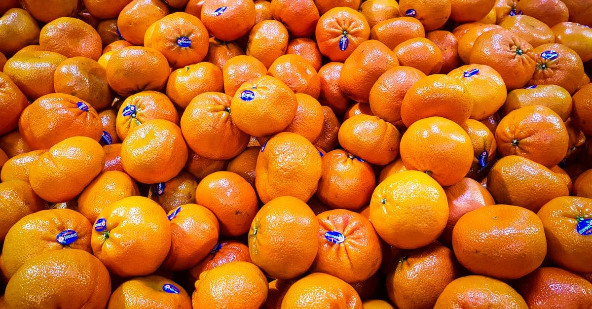 A bunch of oranges sitting on top of a pile of snow