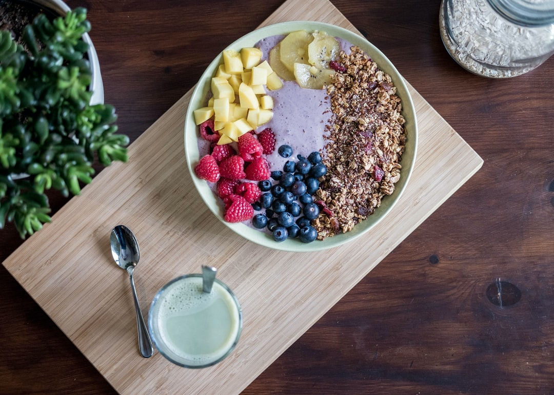 A bowl of fruit sitting on top of a wooden cutting board